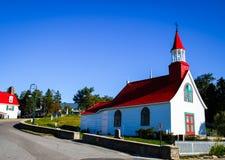 Liten röd och vit kyrka i tadoussac Kanada på en bakgrund för blå himmel Royaltyfri Bild