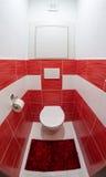 Liten röd och vit toalett royaltyfri fotografi