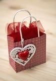 Liten röd påse med ett dekorativt motiv av en hjärta på wood bakgrund Royaltyfria Foton