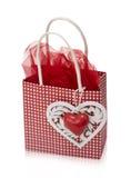 Liten röd påse med ett dekorativt motiv av en hjärta på wood bakgrund Royaltyfri Foto