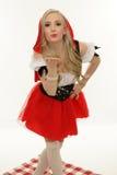 Liten röd ridninghuv som blåser en kyss Royaltyfri Foto