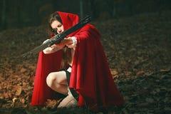 Liten röd ridninghuv som siktar med armborst Arkivfoto