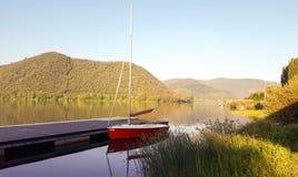Liten röd segelbåt på lagoen di Piediluco Italien royaltyfri bild
