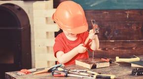 Liten repairman i seminarium Skyddande framsida för hjälmnederlagpojkar Att bulta för unge spikar in i trä royaltyfri foto