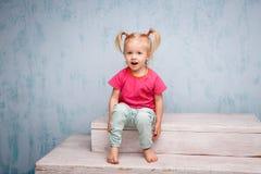 Liten rolig blåögd flickabarnblondin med hästsvansar för en frisyr två på hennes head sammanträde på ett skvaller på bakgrunden a Arkivfoto