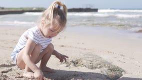 Liten rolig flicka som spelar på stranden nära havet stock video