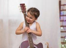 liten rolig le flicka i snöflingadräkt med den akustiska gitarren i musikalisk skola royaltyfri fotografi