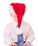 Liten rolig pojke i den röda santa för jul hatten Arkivfoto