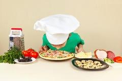 Liten rolig pojke i kockhatt som sniffar lagad mat pizza Arkivbild