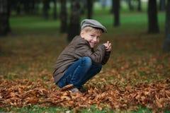 Liten rolig pojke i stående för höstsidor Royaltyfri Bild