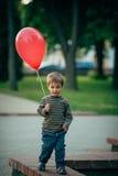 Liten rolig pojke med den röda ballongen Arkivbild