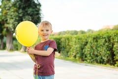 Liten rolig pojkelek med den utomhus- gula ballongen Arkivbilder