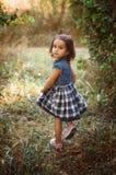 Liten söt flicka som går i en skog Royaltyfri Bild