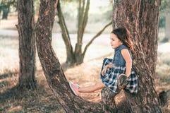 Liten söt flicka som går i en skog Arkivbild
