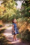 Liten söt flicka som går i en skog Arkivfoton