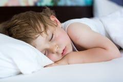 Liten söt litet barnpojke som sover i hans säng Arkivfoton