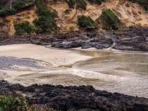 Liten sandig strand mellan steniga klippor Arkivfoton