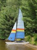 Liten segelbåt på kust av en sjö Arkivfoton