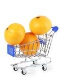 Liten shoppingvagn med tre orange mandarins Fotografering för Bildbyråer