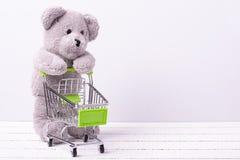 Liten shoppingvagn och en nallebjörn Begreppsmässig bild som är till salu av leksak- eller barns fantasier royaltyfri foto