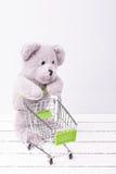 Liten shoppingvagn och en nallebjörn Begreppsmässig bild som är till salu av leksak- eller barns fantasier royaltyfri bild
