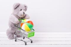Liten shoppingvagn och en nallebjörn Begreppsmässig bild som är till salu av leksak- eller barns fantasier arkivfoton
