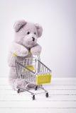 Liten shoppingvagn och en nallebjörn Begreppsmässig bild som är till salu av leksak- eller barns fantasier arkivbilder