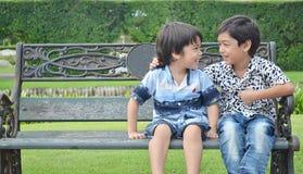 Liten siblingpojke som skrattar i trädgården Arkivfoton