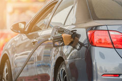 Liten silverbil som tankar på bensinstationen Arkivbild