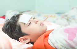 Liten sjuk pojke med temperaturtermometern i mun Arkivbild
