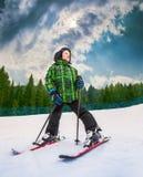 Liten skidåkare i berghimmelsemesterort med stor himmelbakgrund Arkivfoton