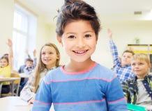 Liten skolaflicka över klassrumbakgrund royaltyfria foton