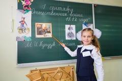 Liten skolaflicka Anya 7 år gamla ställningar på svart tavla royaltyfri fotografi