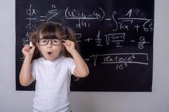 Liten skolaflicka i klassrum smart unge arkivbilder