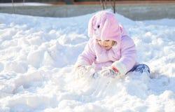 Liten skolaflicka som spelar med snö Arkivfoton