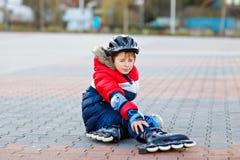 Liten skolaungepojke som åker skridskor med rullar i staden barn i skyddssäkerhetskläder Aktiv skolpojkeframställning royaltyfri bild