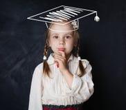 Liten skolflicka, i att tänka för avläggande av examenhatt arkivbilder