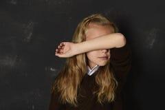 Liten skolflicka i enhetlig beläggning hennes framsida med hennes arm som gråter det ledsna offret av pennalismen på skolan Royaltyfri Foto
