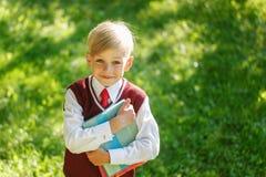 Liten skolpojke för stående på naturbakgrund Barn med böcker och den klädda likformign Utbildning för ungar tillbaka begreppsskol Royaltyfri Bild
