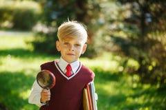 Liten skolpojke för stående på naturbakgrund Barn med böcker och loupen Utbildning för ungar tillbaka begreppsskola till Royaltyfri Bild