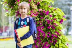 Liten skolpojke med böcker och ryggsäcken som känner sig mycket upphetsade om att gå tillbaka till skolan Arkivbild