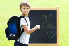Liten skolpojkehandstil på svart tavla Utbildning tillbaka till skolabegreppet Arkivfoto