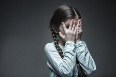 Liten skrämd flicka som kikar till och med fingrar Royaltyfri Foto