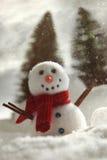 Liten snögubbe med snöbakgrund Royaltyfria Bilder