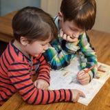 Liten snillepojkehjälp hans broder med läxa Royaltyfri Foto