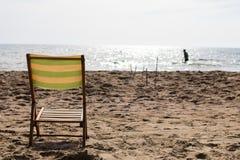 Liten solstol på sanden av en strand med havet Royaltyfri Foto