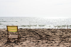 Liten solstol på sanden av en strand med havet Arkivbilder