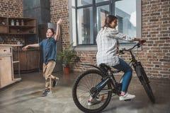 Liten son och hans härlig moder som har roligt och rider cykeln arkivbild