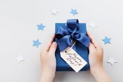 Liten son som rymmer en gåva eller en närvarande ask med den lyckliga etiketten för hälsning för faderdag fotografering för bildbyråer