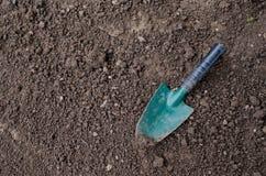 Liten spade på trädgårds- jord Royaltyfri Bild